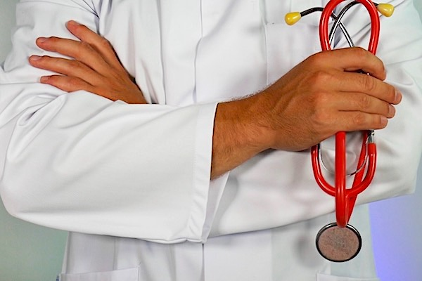 Man in white coat holding a stethoscope