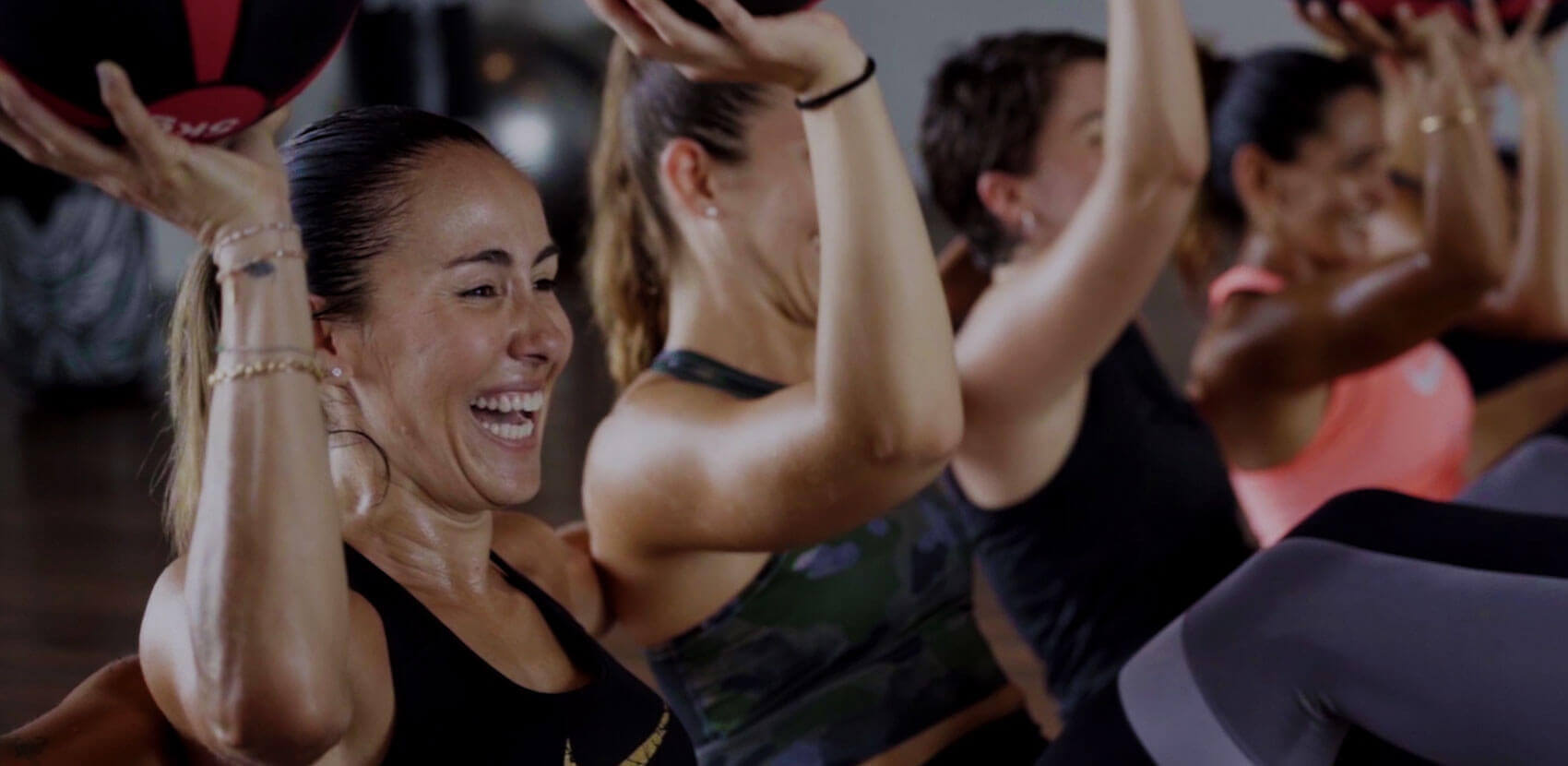 Mujer sonriente y sudada agarra una pelota medicinal y practica entrenamiento funcional
