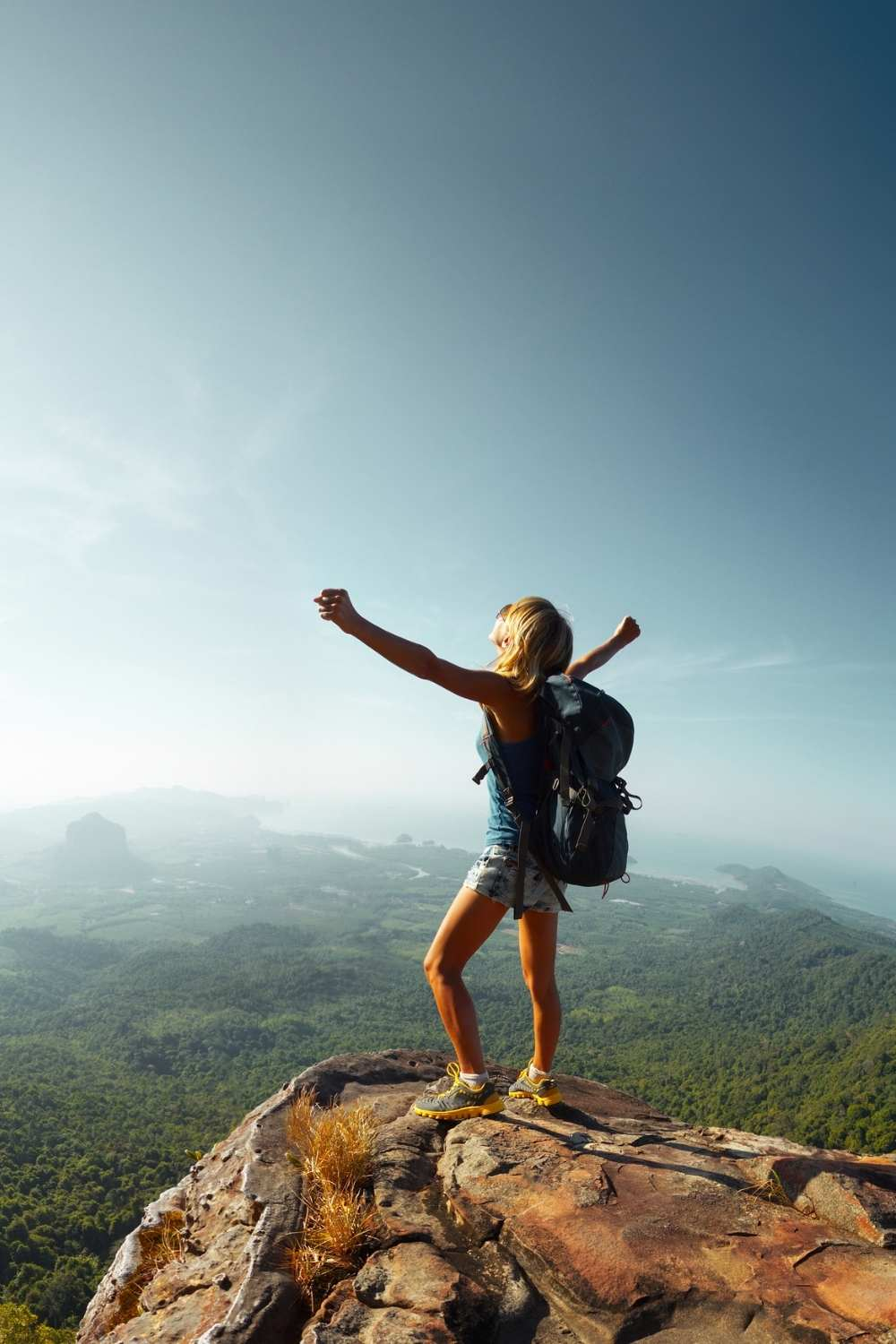 woman hiker celebrating on a mountain