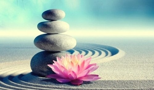 Stacked rocks in sand with pink flower at base