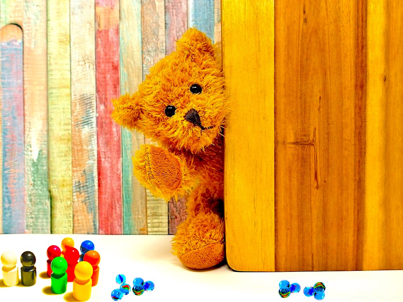 Teddy bear next to some miniature skittles and marbles