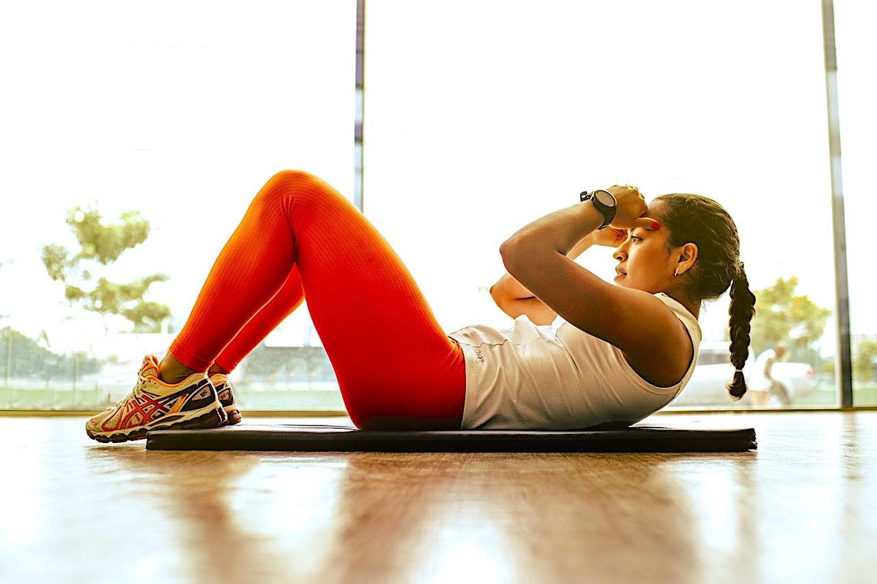 Woman wearing orange leggings lying on floor mat exercising by a window