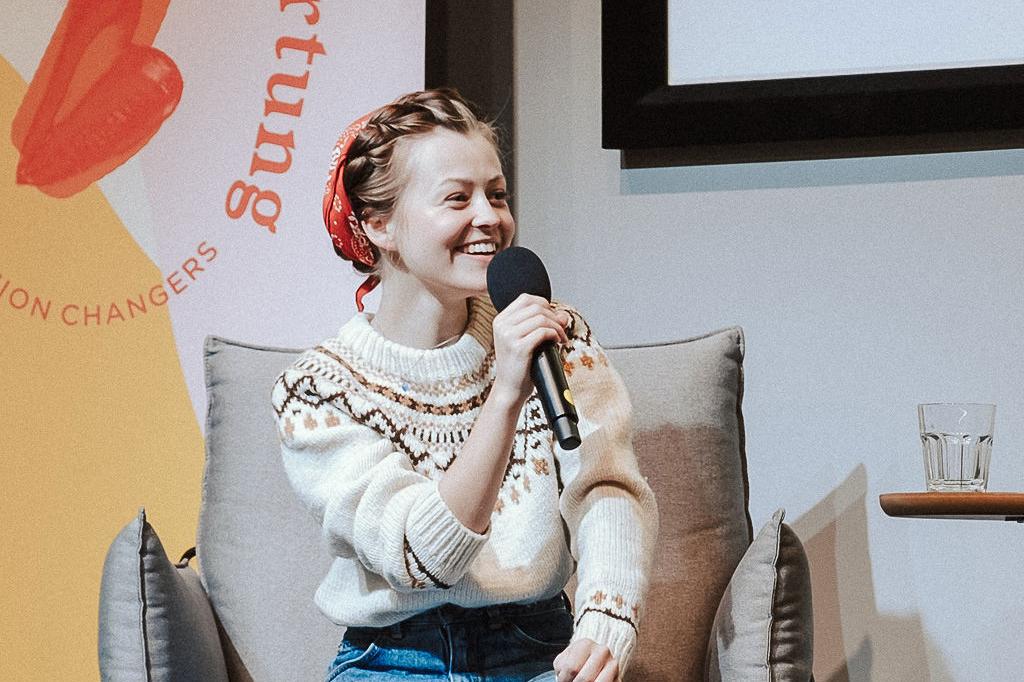 Clara Mayer sitzt auf der Fashion Changers Konferenzbühne und spricht über Aktivismus