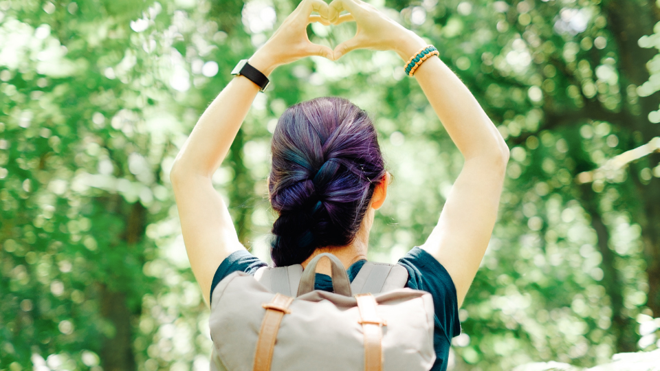 Girl in a forest making heart sign with her hands above her head