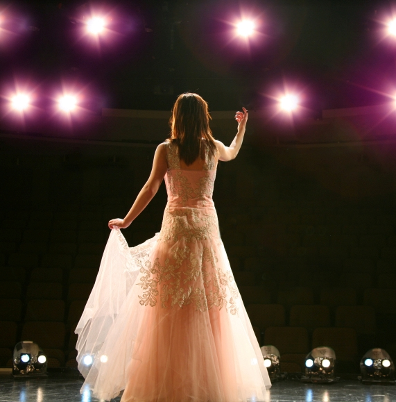 Female singer in a lace dress singing to the audience on a brightly lit stage