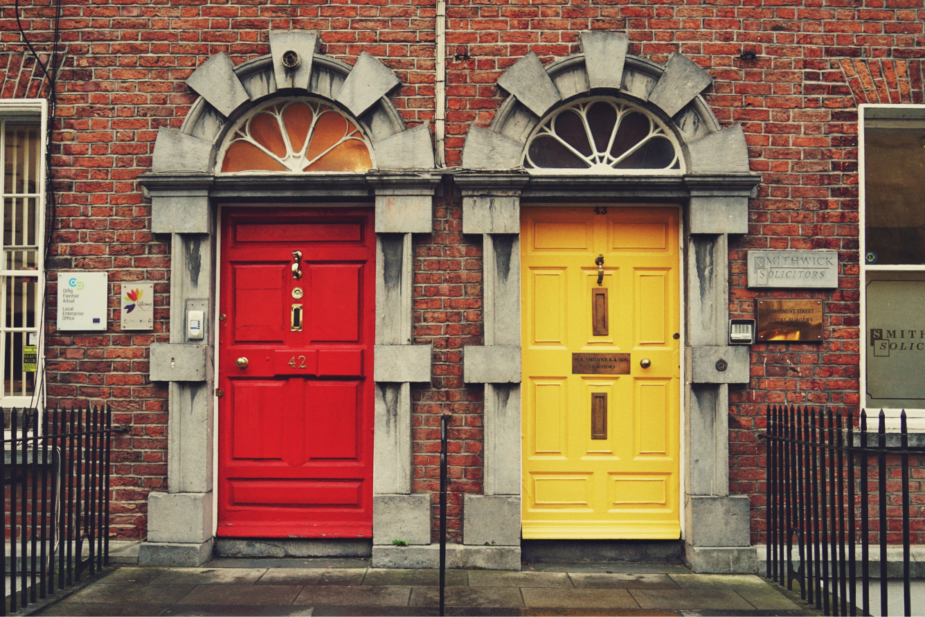 A red door and a yellow door on a terraced building