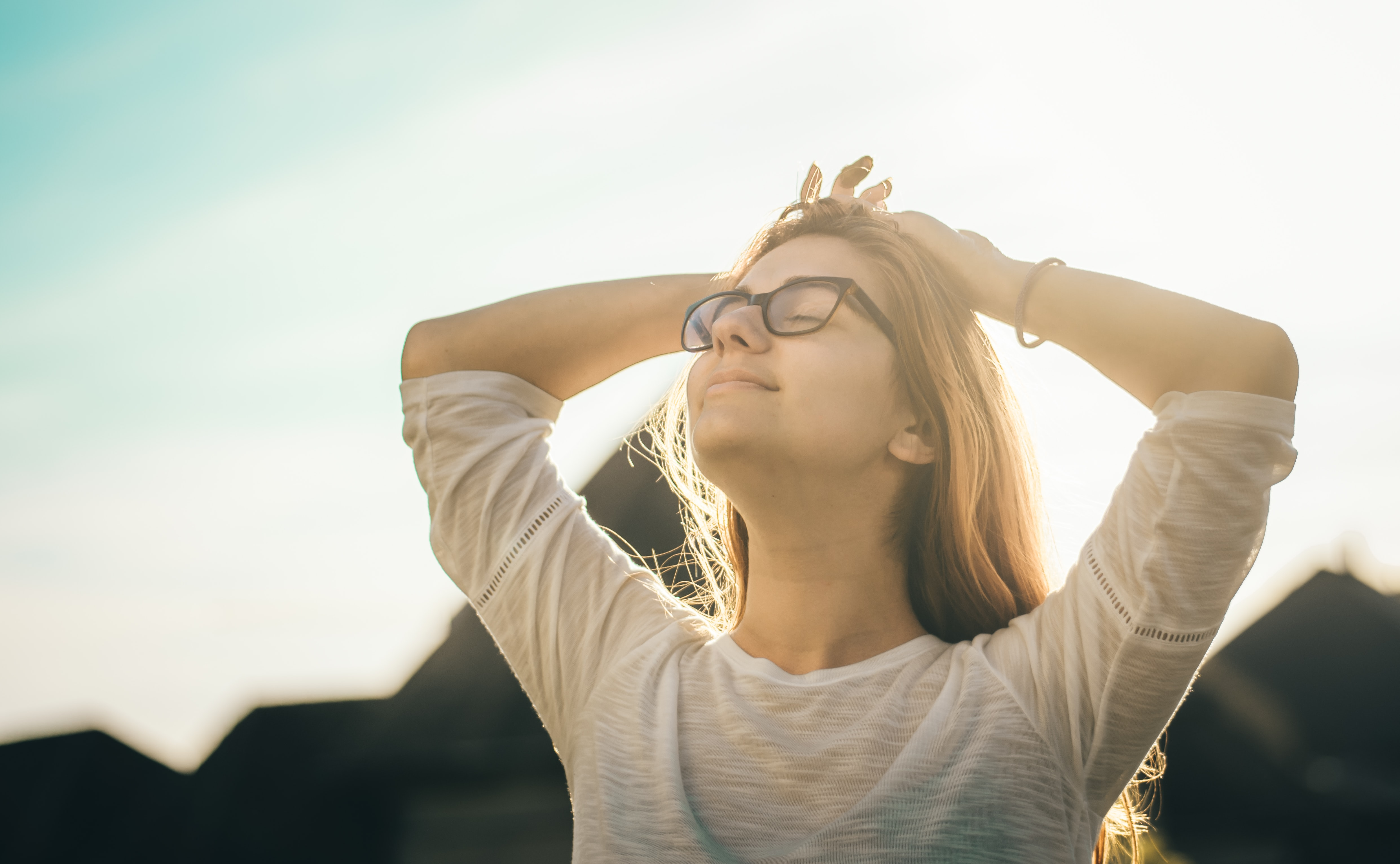 Young woman with eyes closed, turns her face up to the sun, with her hands on her head