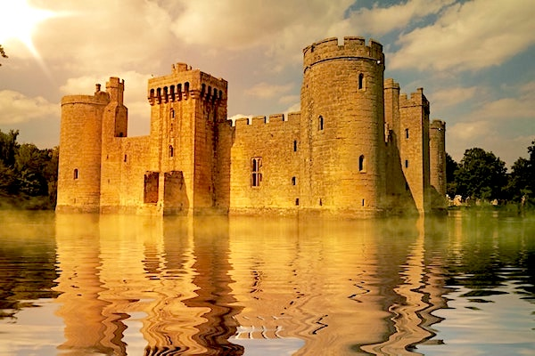 Old golden stone castle with a large moat of water in front of it