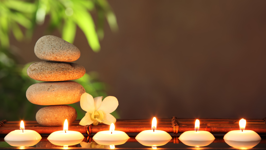 Stack of rocks on bamboo with floating candles