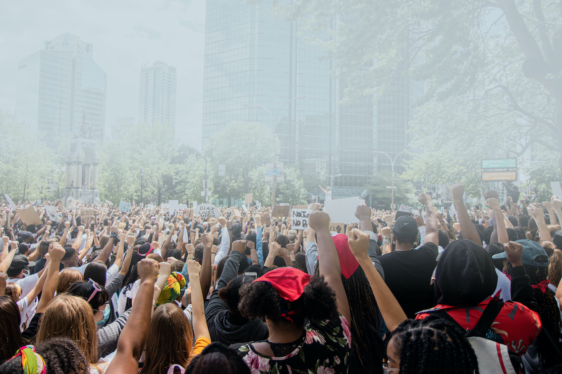 Hundreds of people raise fists at a Black Lives Matter demonstration