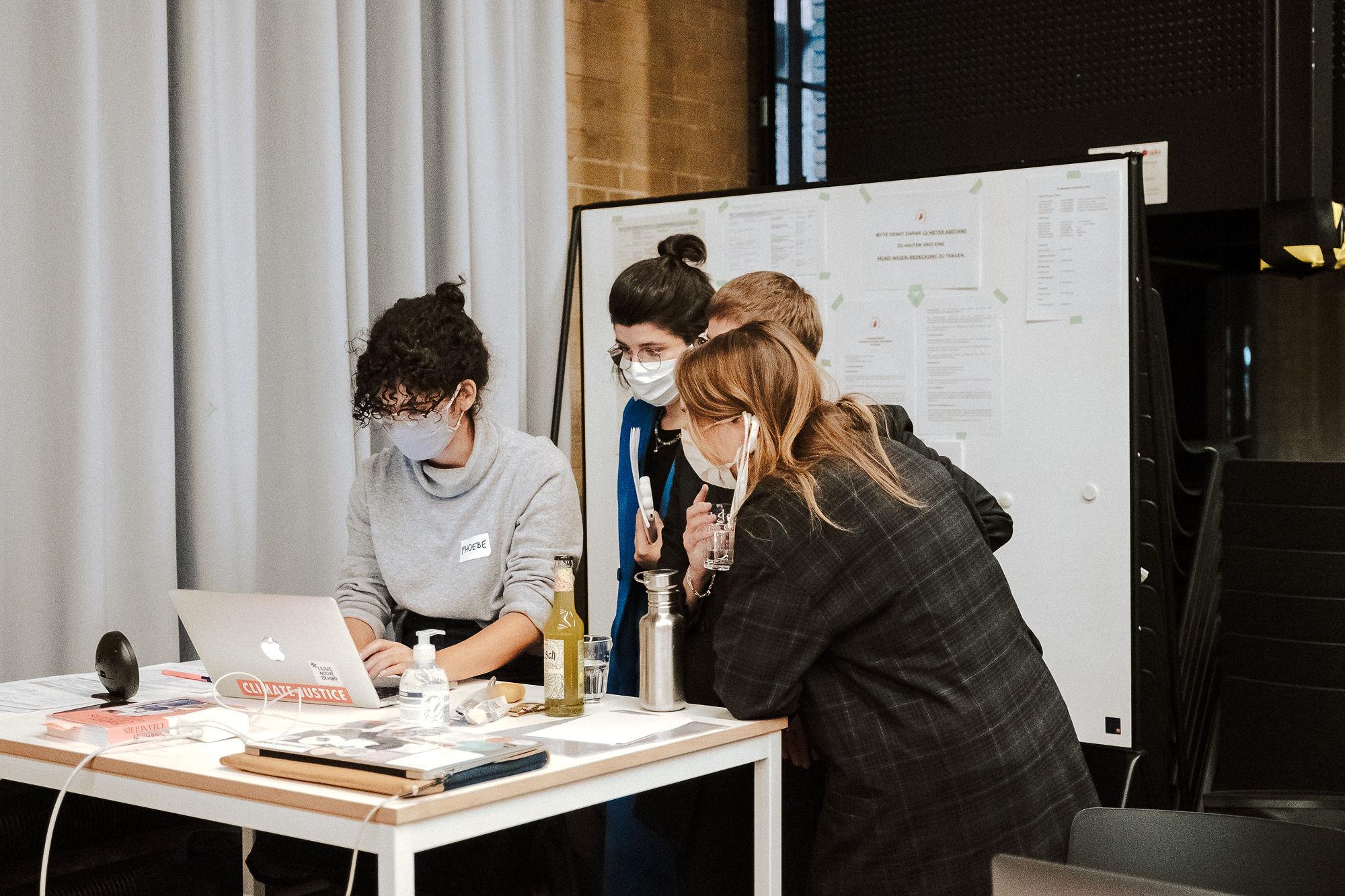 Die drei Fashion Changers Gründerinnen stehen mit Phoebe Nicette vor einem Laptop und besprechen sich