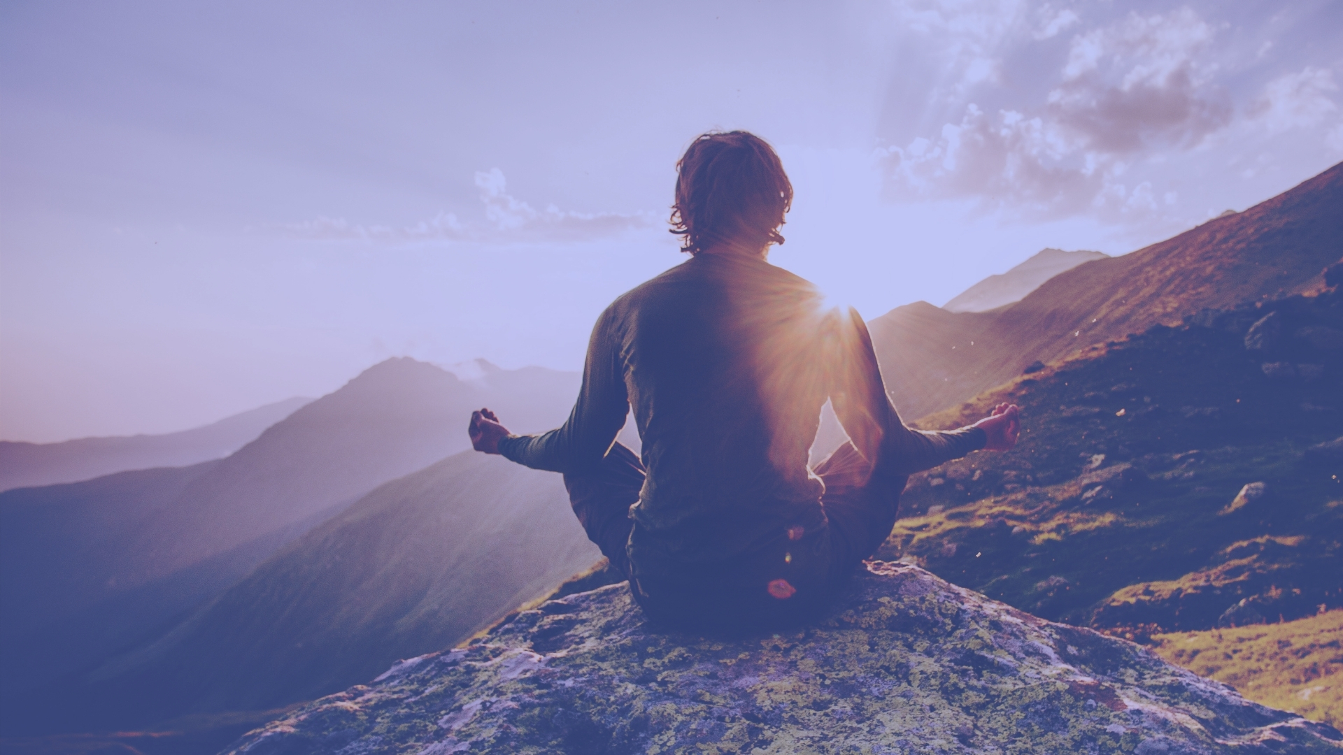 Person meditating in beautiful mountain landscape.