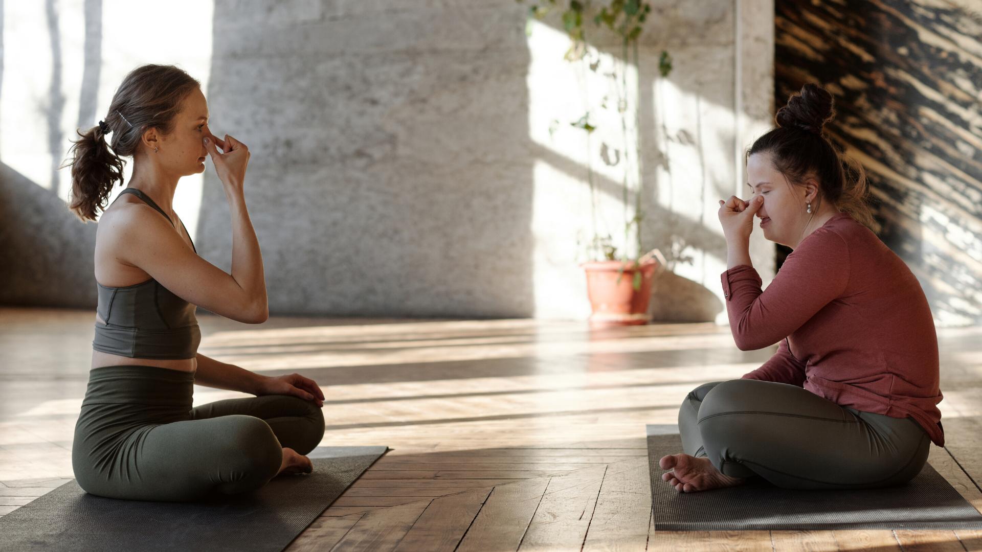 Yoga teacher with student