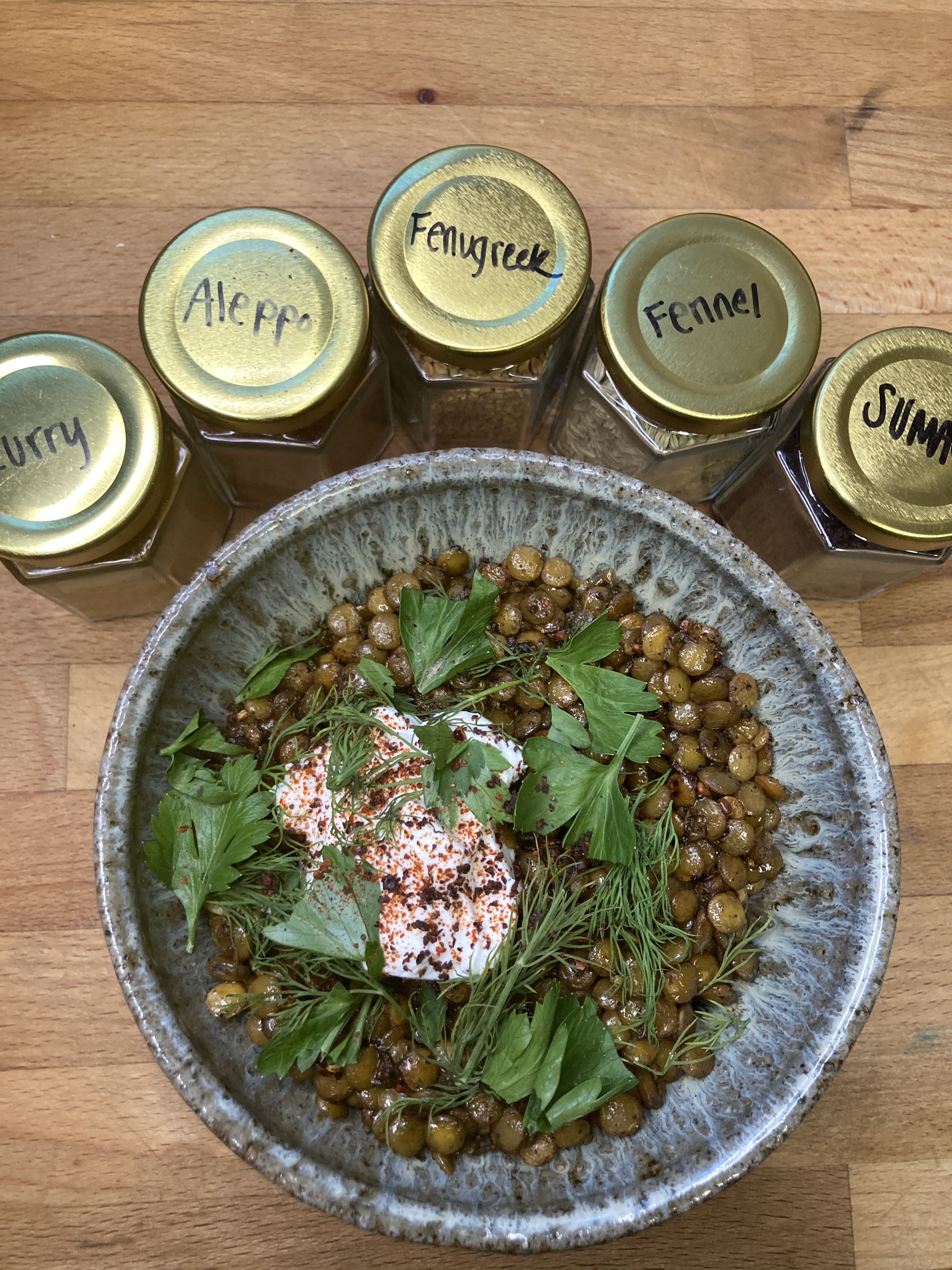 Hearty bowl of lentils with yogurt, dill and parsley, ringed by an assortment of spices in jars