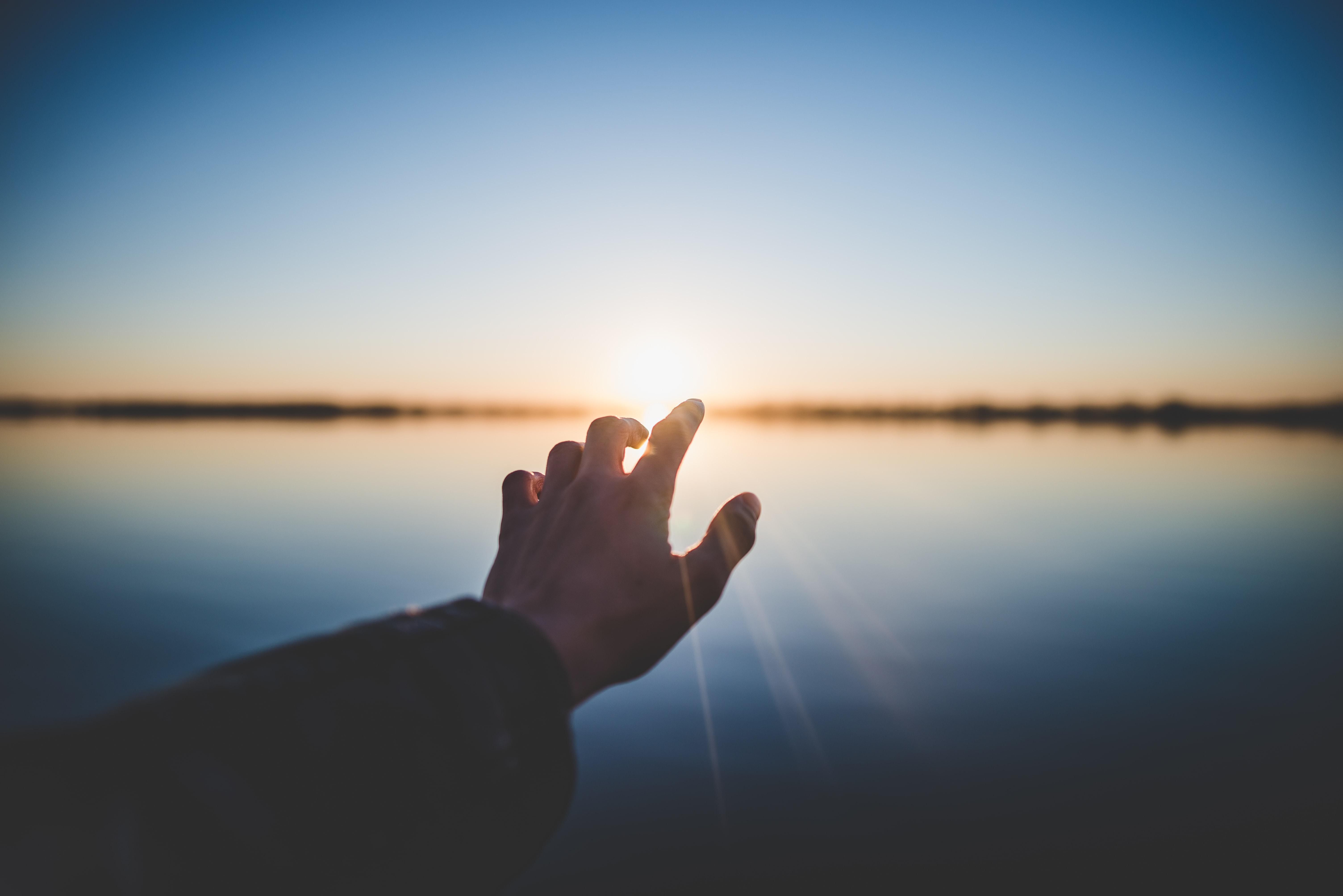 a finger reaching towards sunrise