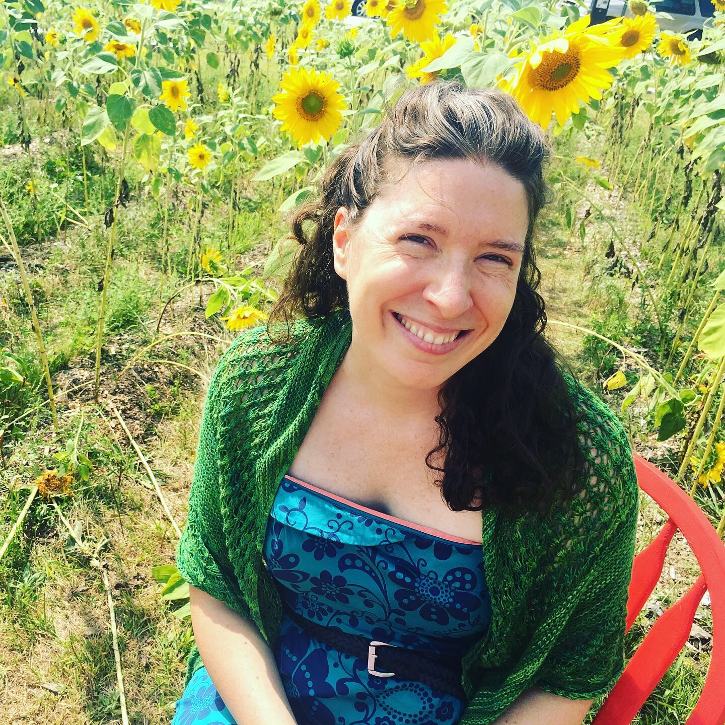 Woman sitting in a red chair in front of a field of sunflowers.