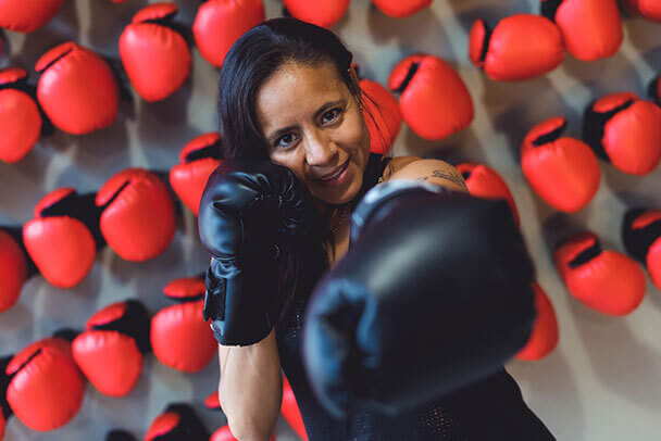 Mujer practica boxeo con guantes de box negros frente a una pared de guantes de box rojos.
