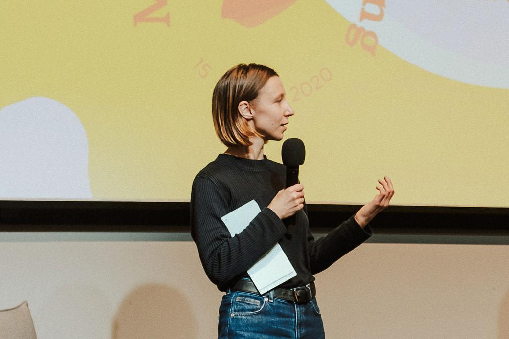 Frau mit schwarzem Oberteil steht auf der Fashion Changers Konferenzbühne und erklärt, wie Lieferketten kreislauffähiger werden können
