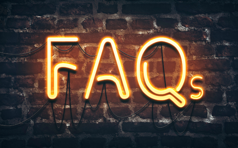 image of neon sign spelling out FAQ on a brick wall