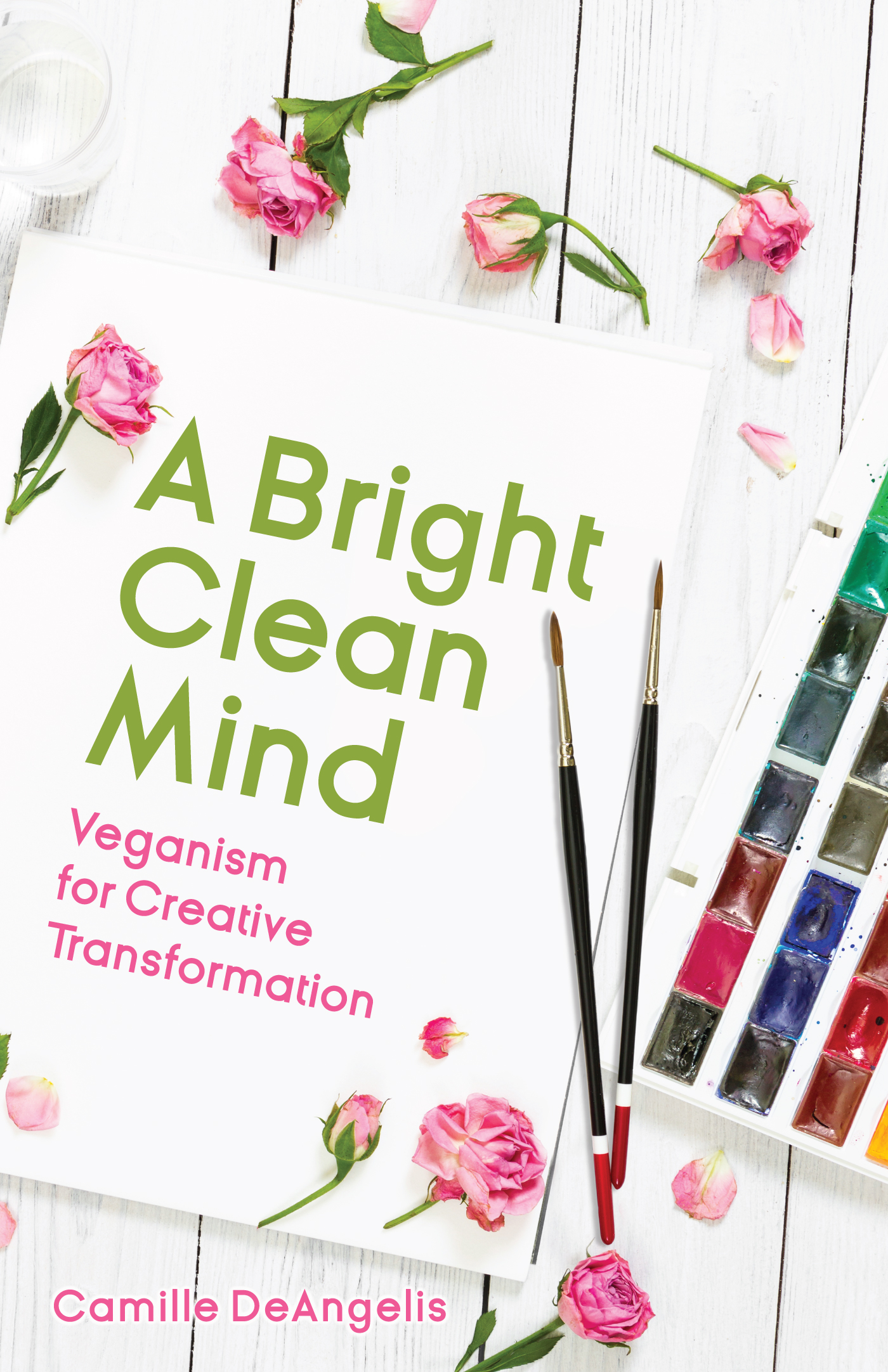 A book cover with pink roses and a watercolor set and paintbrushes on a white table, the book title on a blank sheet of paper: A Bright Clean Mind: Veganism for Creative Transformation.