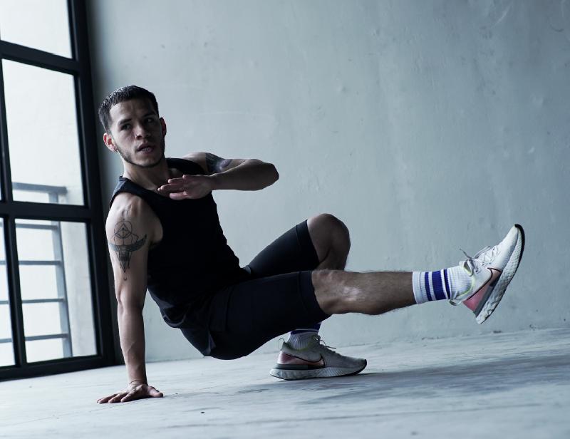 Hombre en ropa deportiva se ejercita en el suelo haciendo uso de su propio peso.
