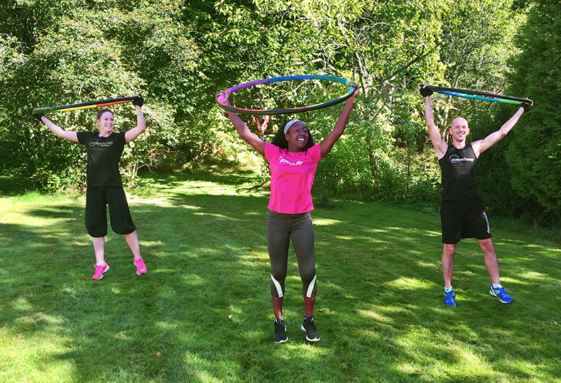 Three people using fitness hoops outdoors