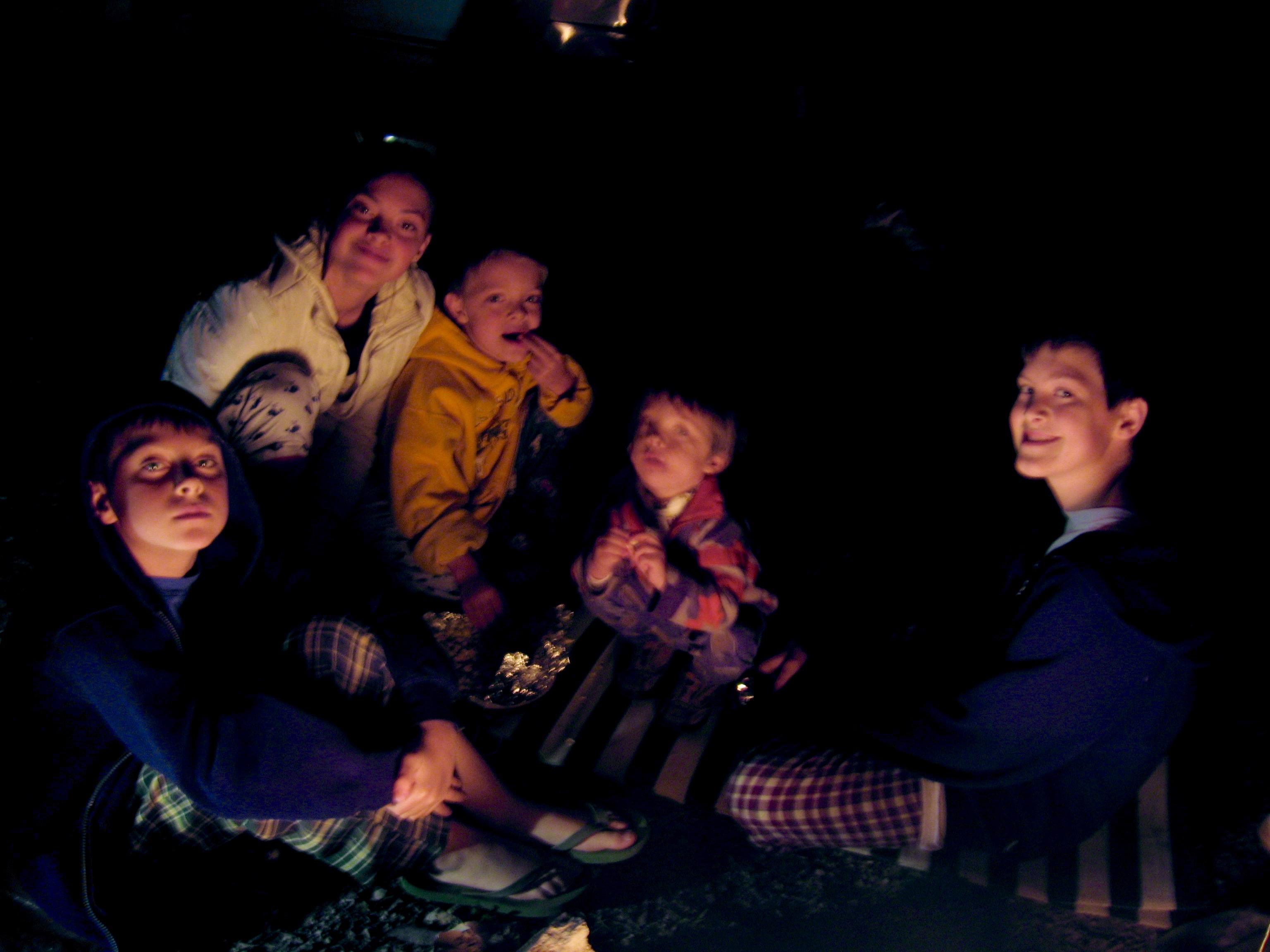 5 kids gathered around a campfire