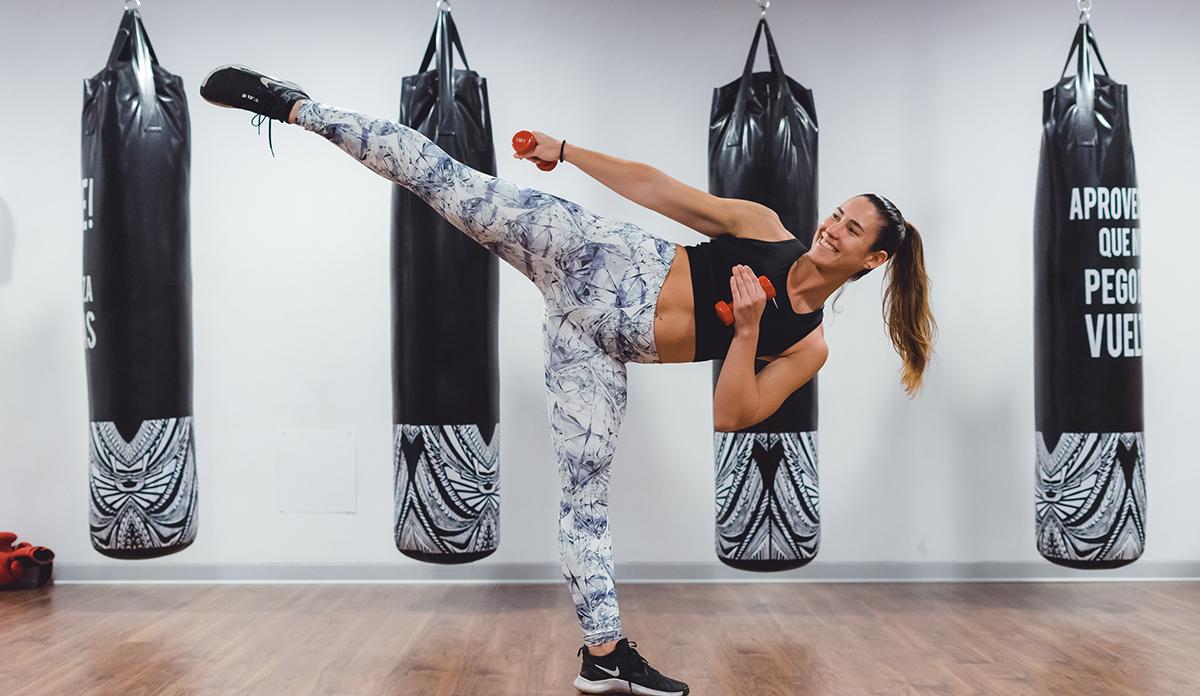 Mujer patea al hacer ejercicio y practicar artes marciales.