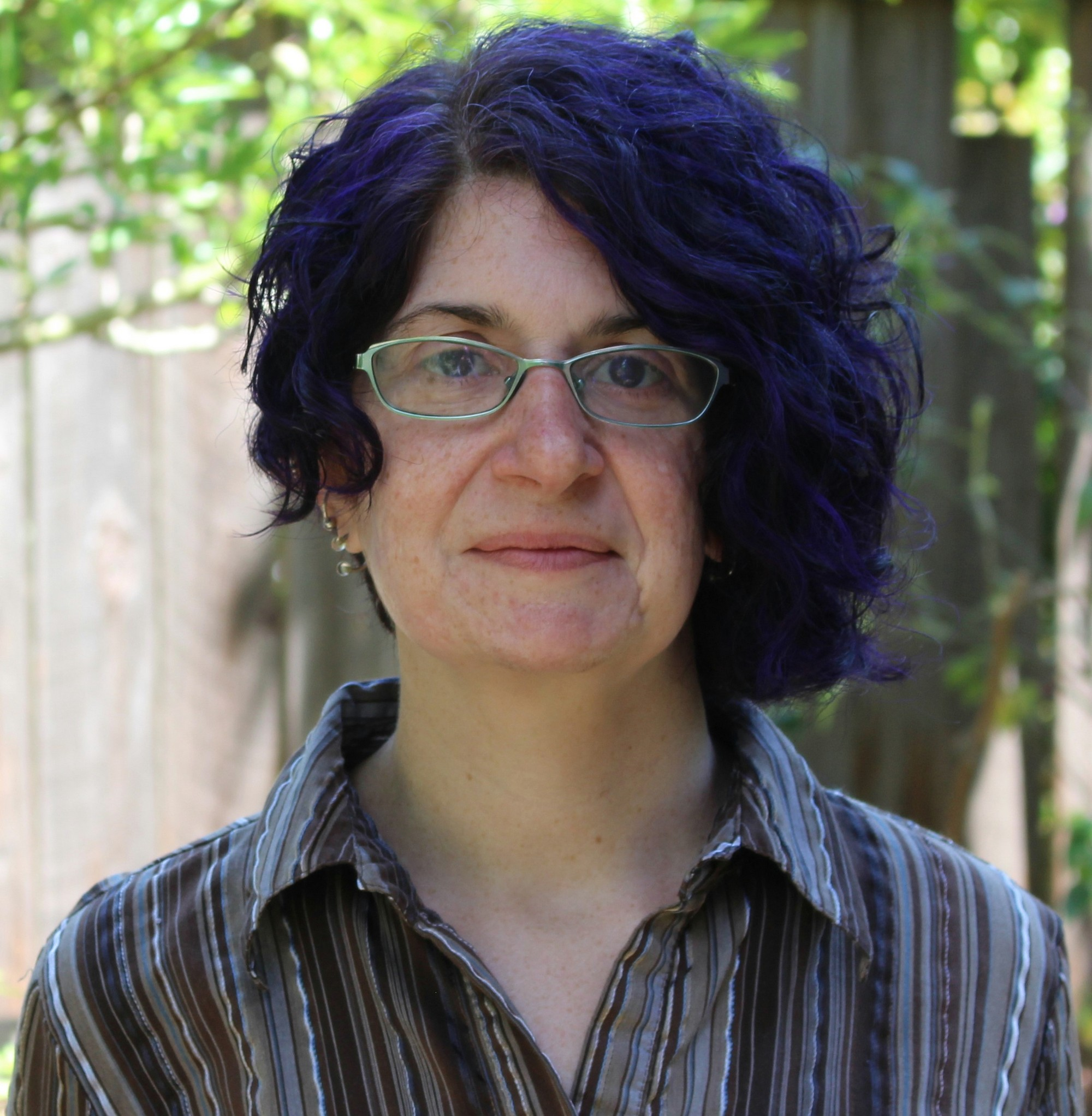 Rachel, a White woman with curly purple hair and glasses, in front of a tree and fence, wearing a warm gaze