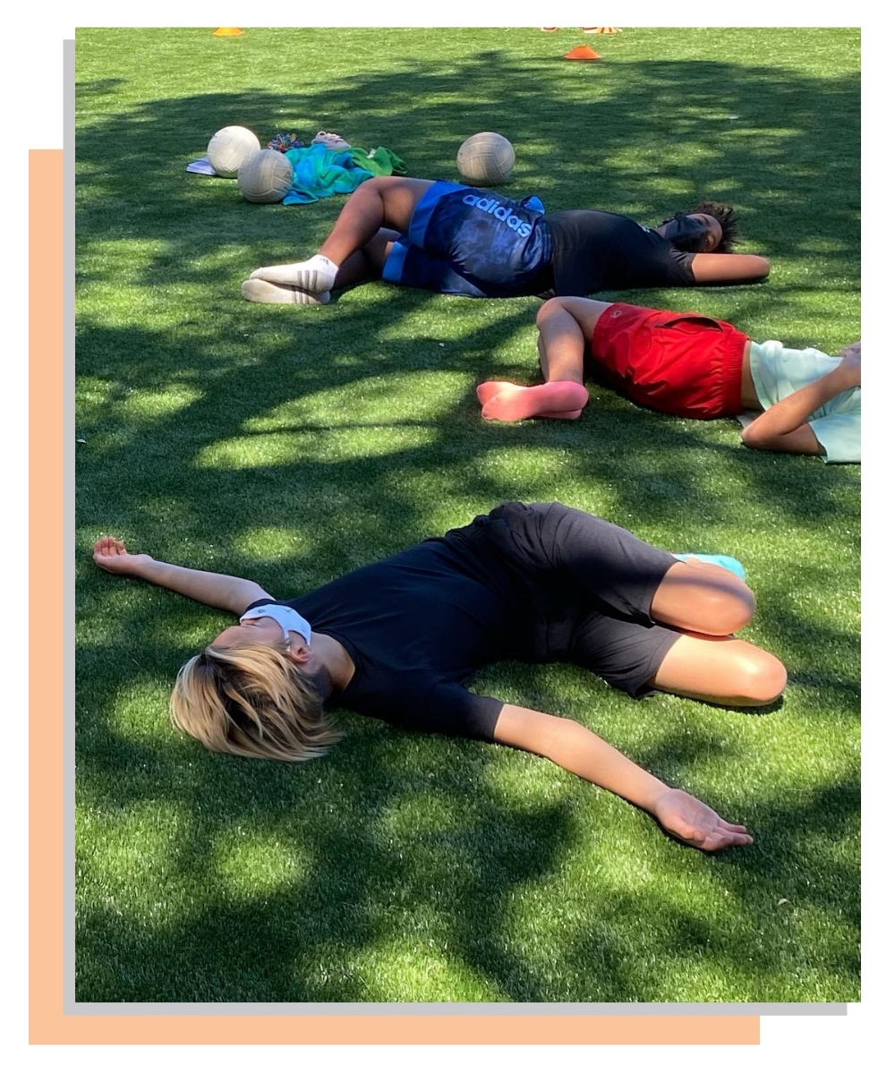 Students lying on grass in a spinal twist