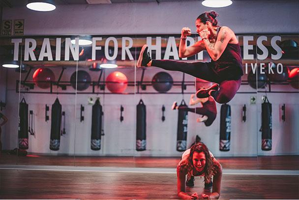 Mujer salta pateando sobre una mujer en plank frente a un espejo con la frase