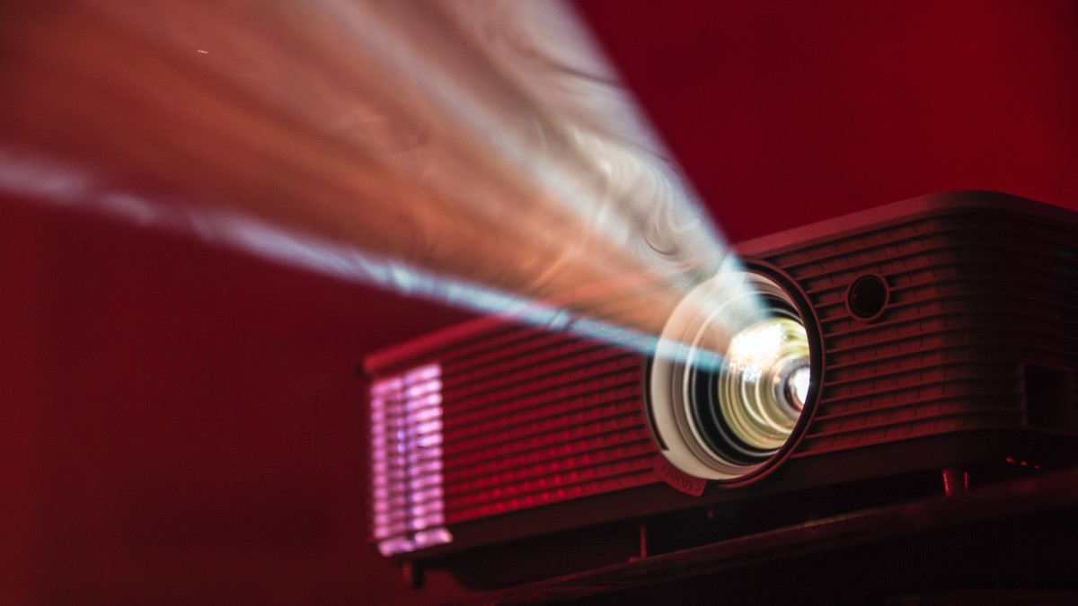 projector with beam of light, in red light