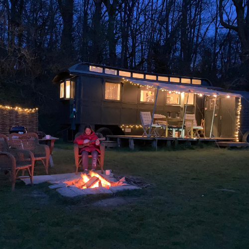 girl sitting at campfire playing ukulele with caravan in background