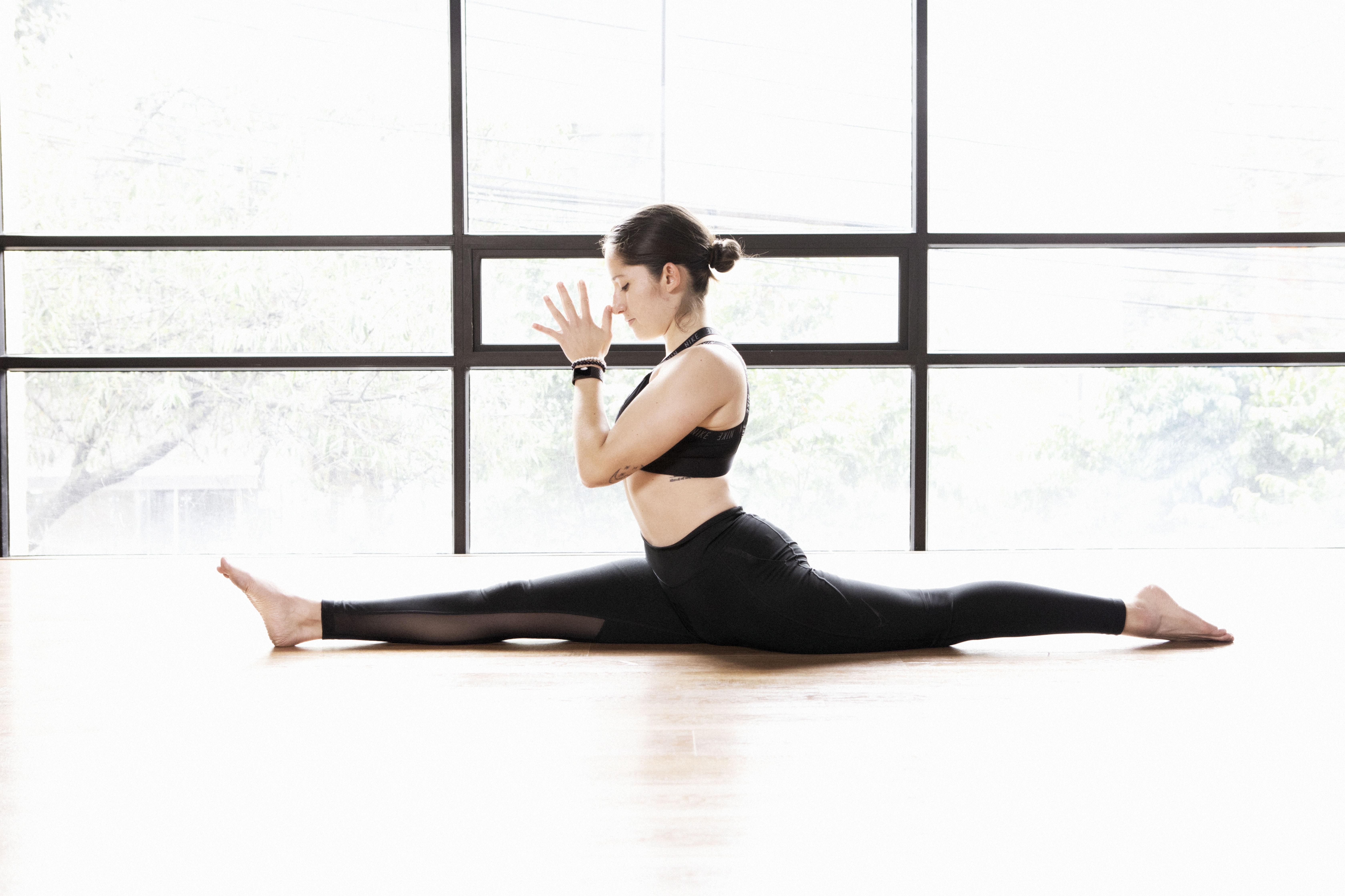 Mujer practica yoga con una abertura de piernas.