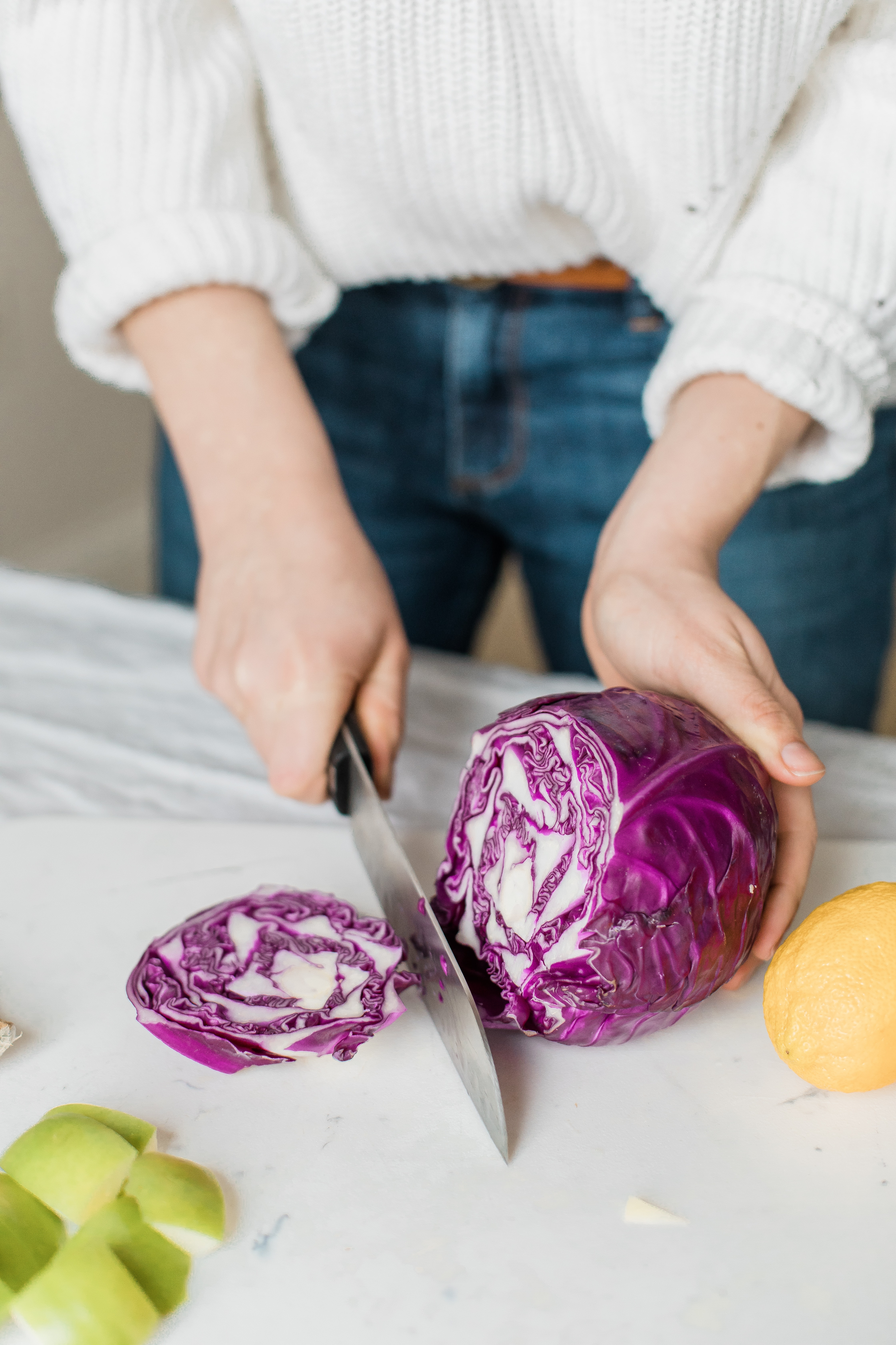 woman's hands cutting purple cabbage with knife