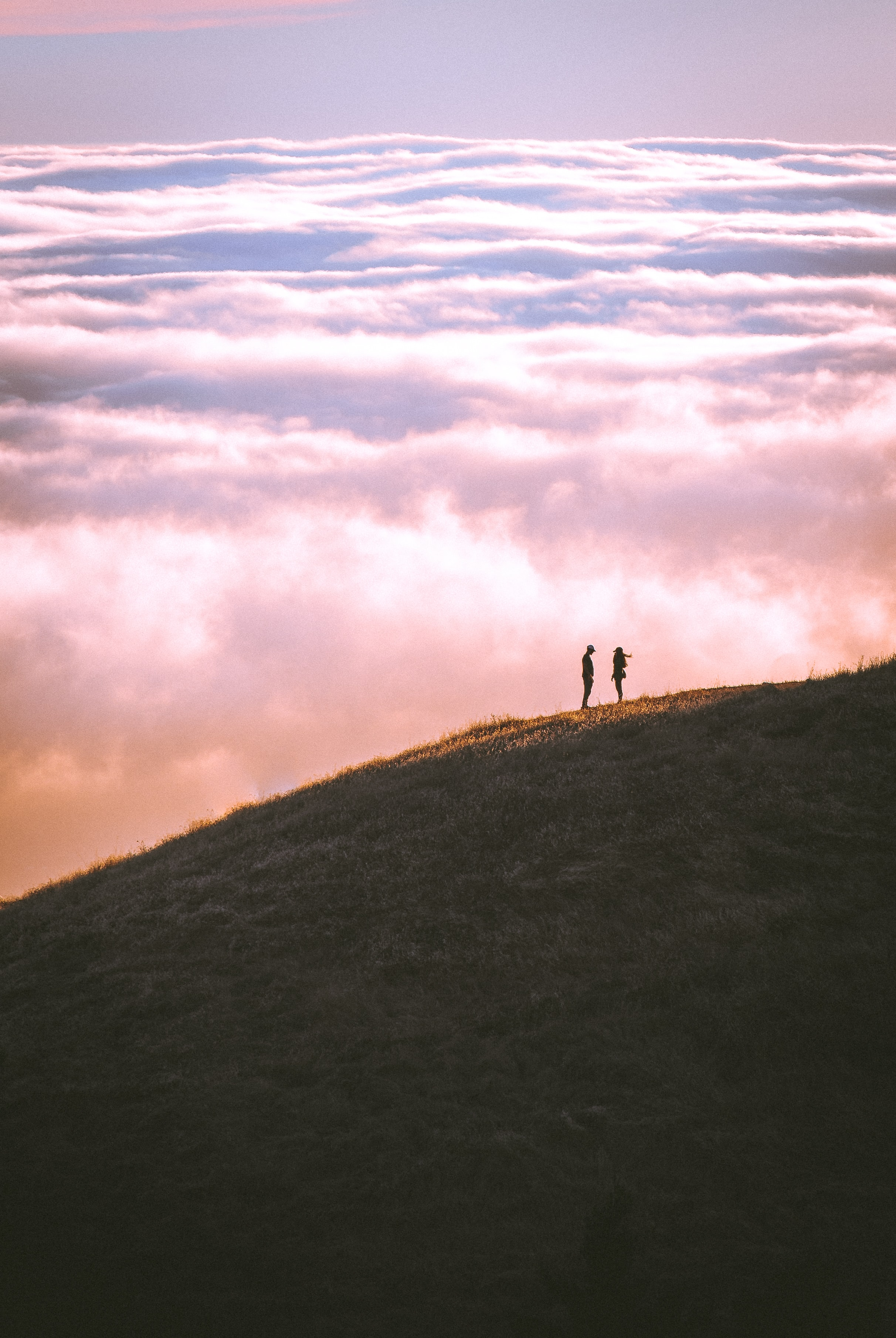 Two people on a hill against a sunset of clouds