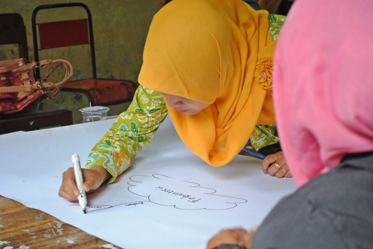 lady drawing on white paper with yellow headscarf, next to lady with pink headscarf