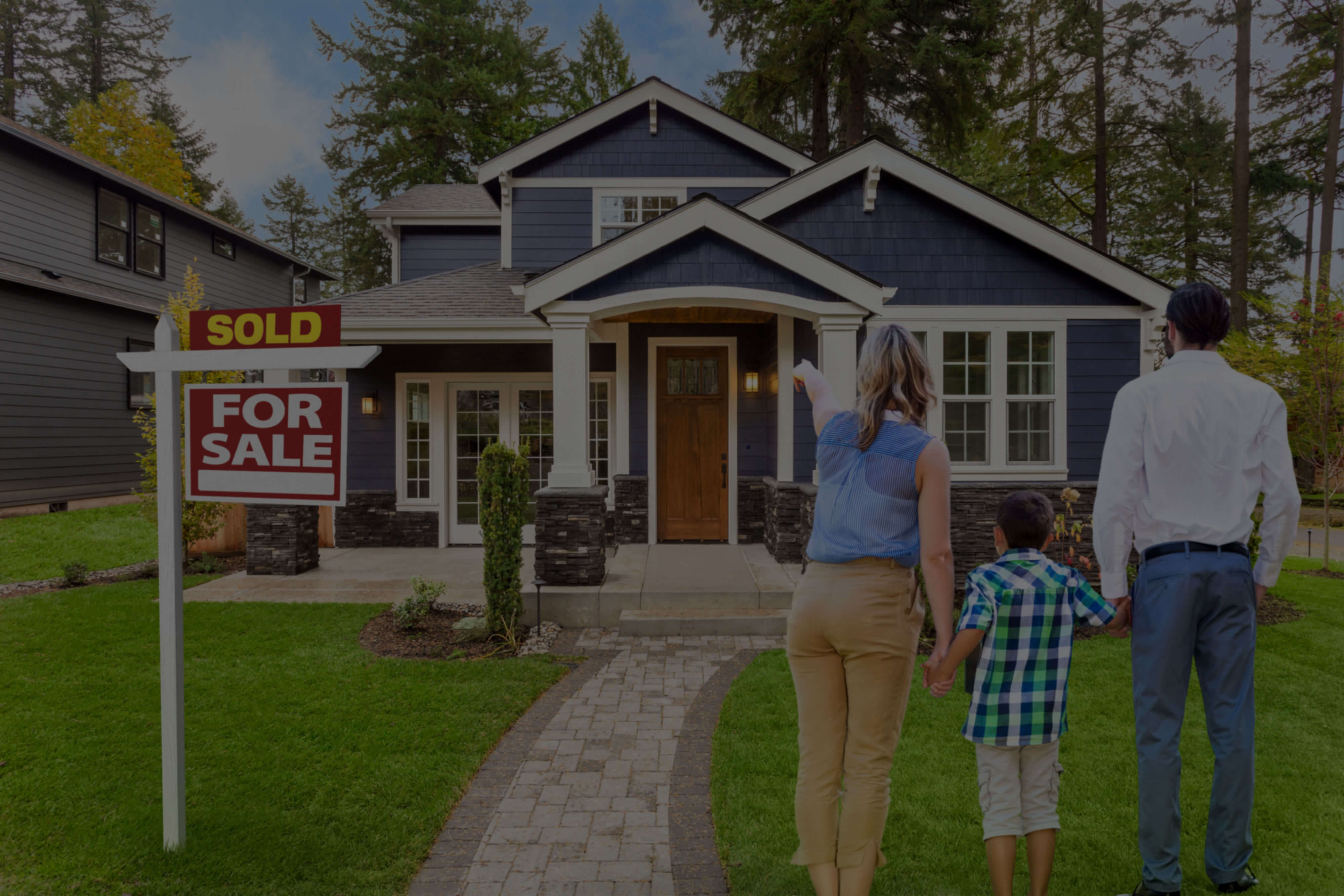 Family in front of home with sold sign
