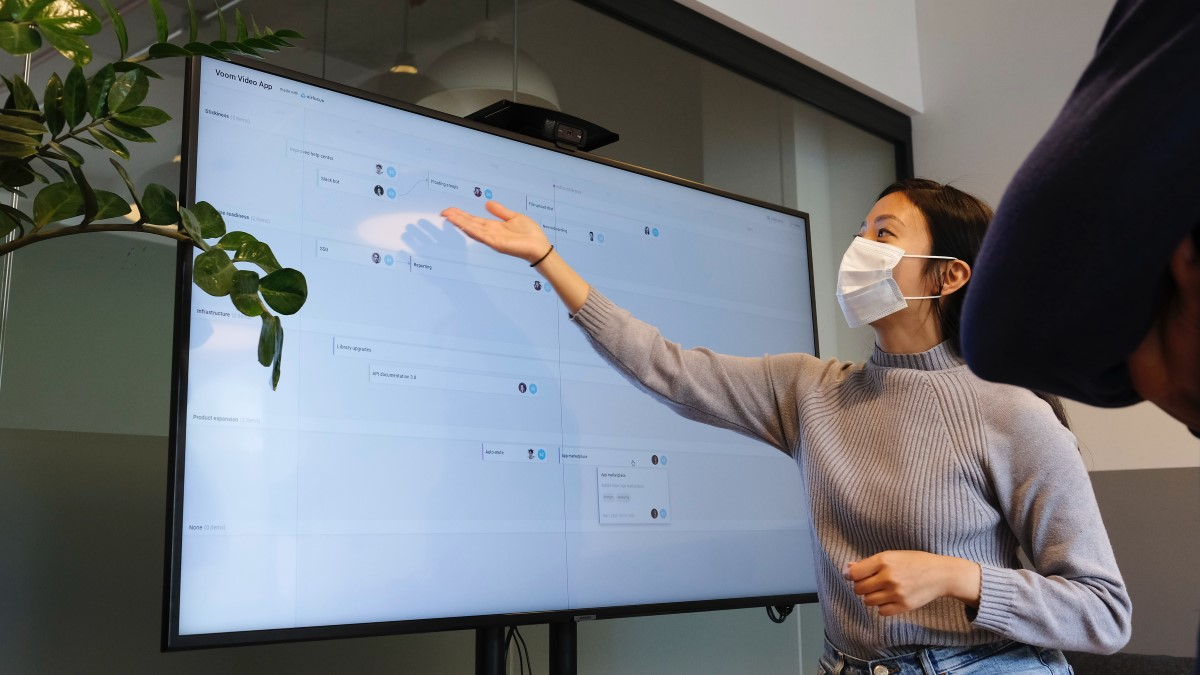 female wearing grey jumper and a mask pointing at a large screen