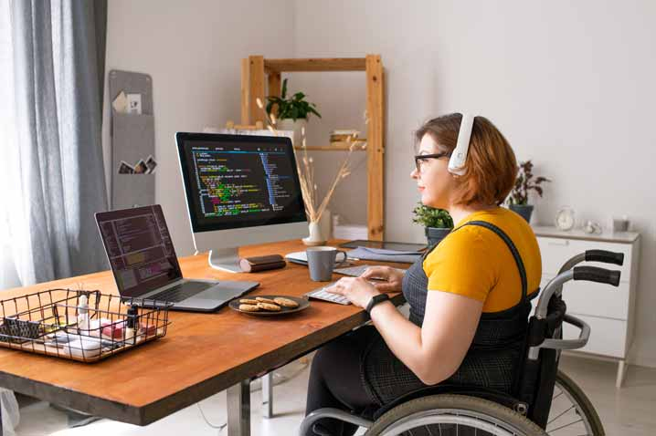 woman at desk in wheelchair working on computer