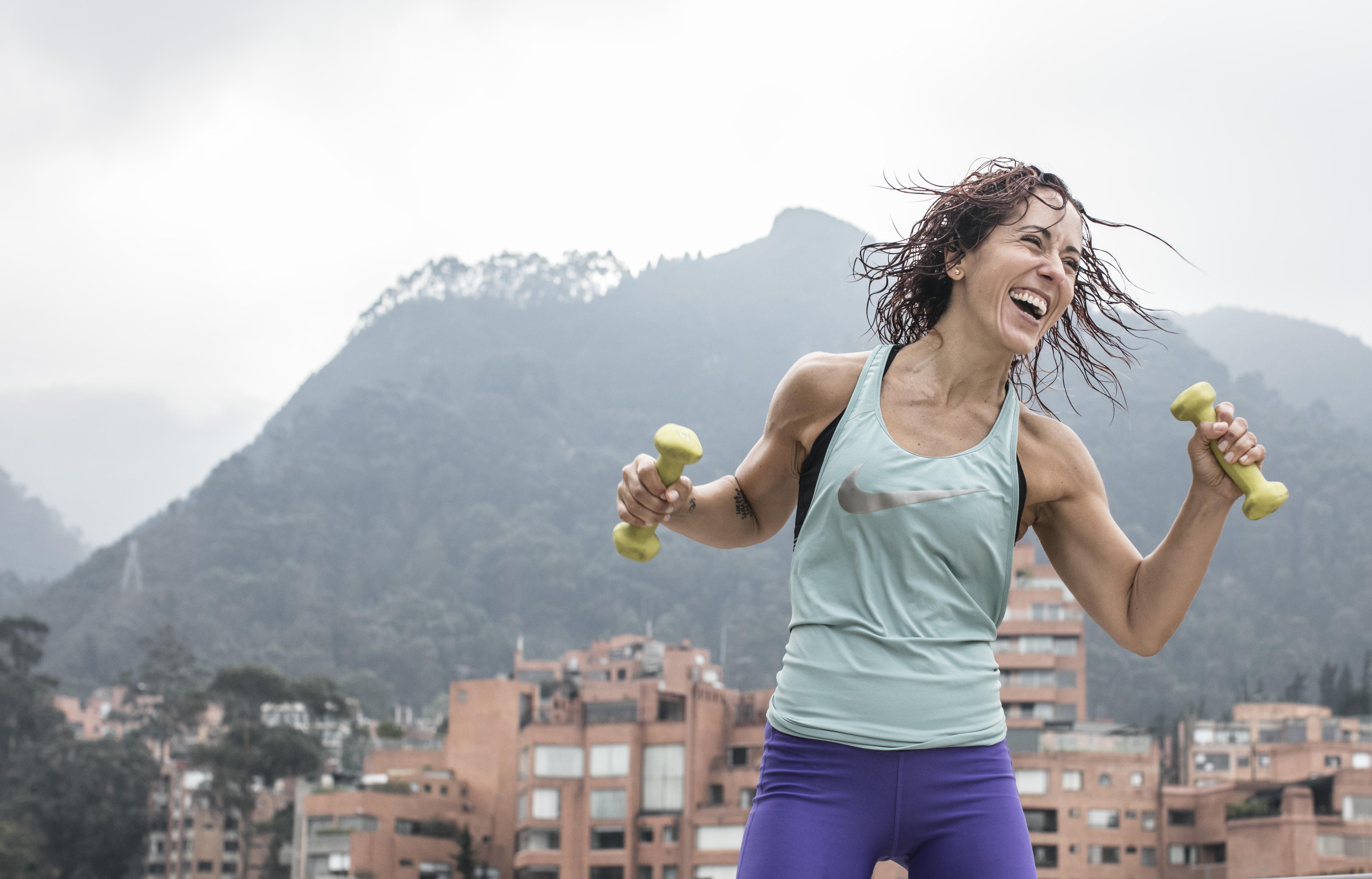 Mujer sonriente practicando deporte con dos mancuernas en las manos y con un polo de Nike.