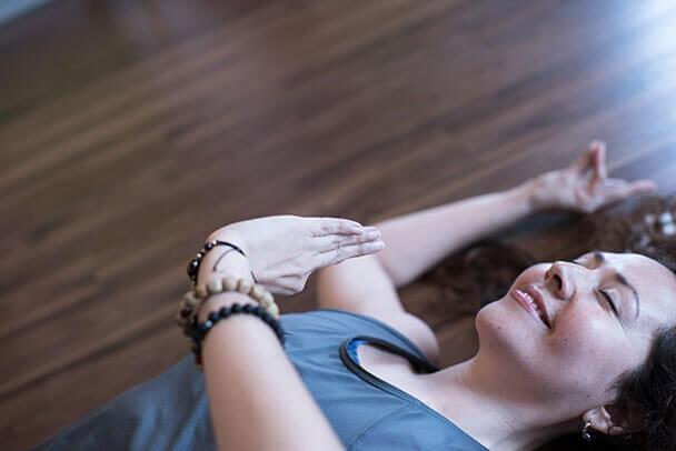 Mujer sonriente practica yoga echada en el piso.