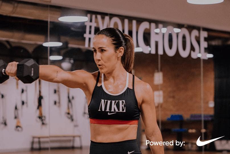 Mujer con top de Nike levanta una pesa y hace entrenamiento funcional