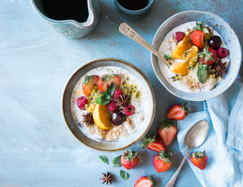Dos bowls de avena con leche cubiertos de frutas variadas.