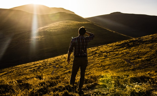 Person hiking in the mountains, sun is shining
