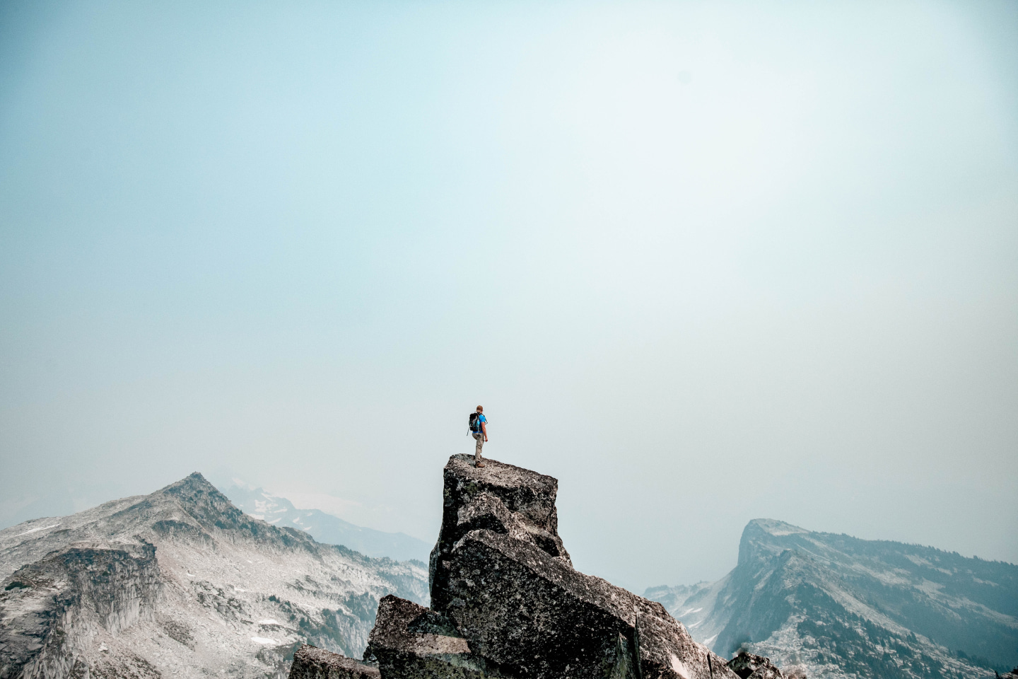 A man stands on top of a mountain cliff edge