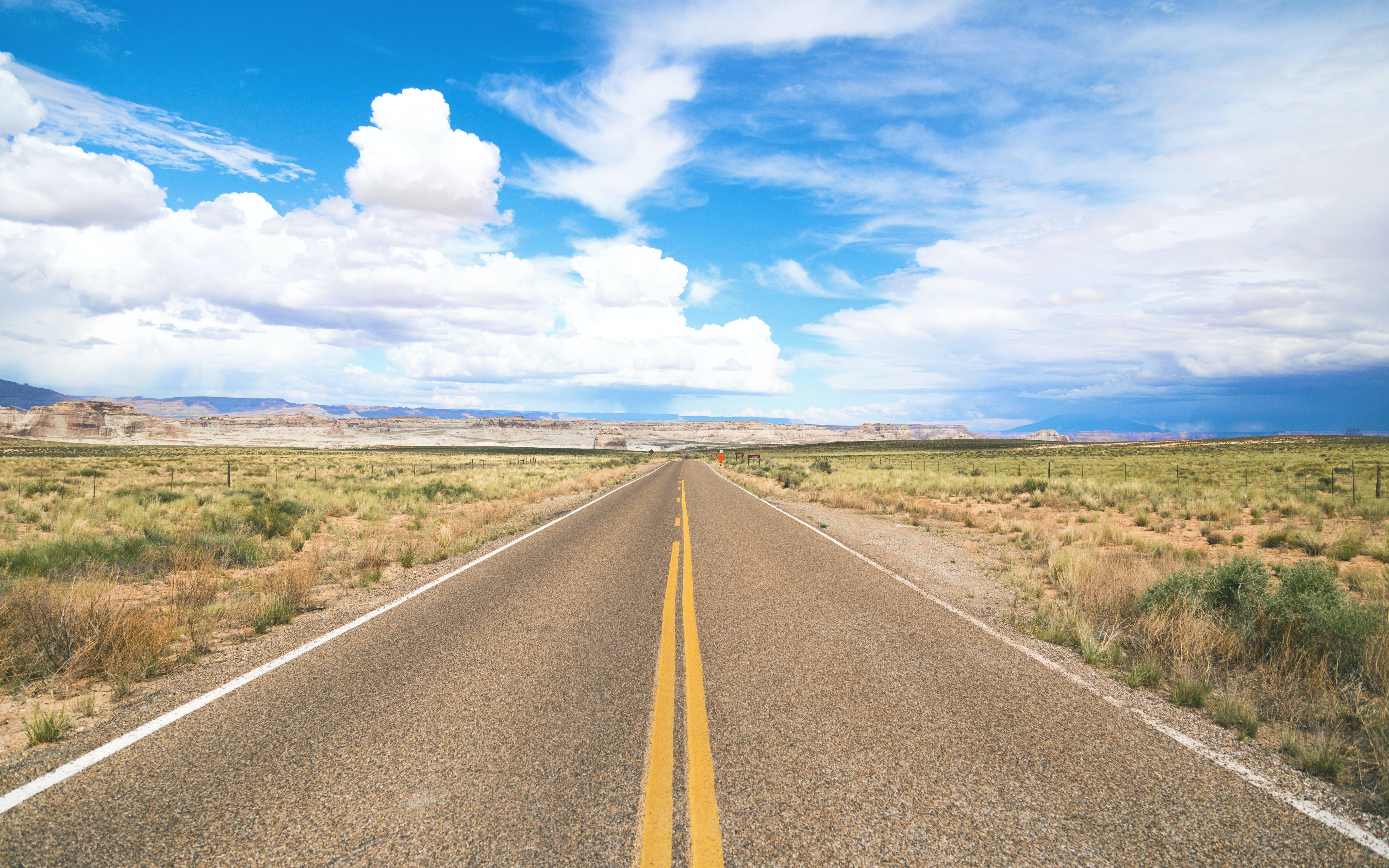 Photo of a cloudy sky with an empty two lane road // Copyright to original photographer