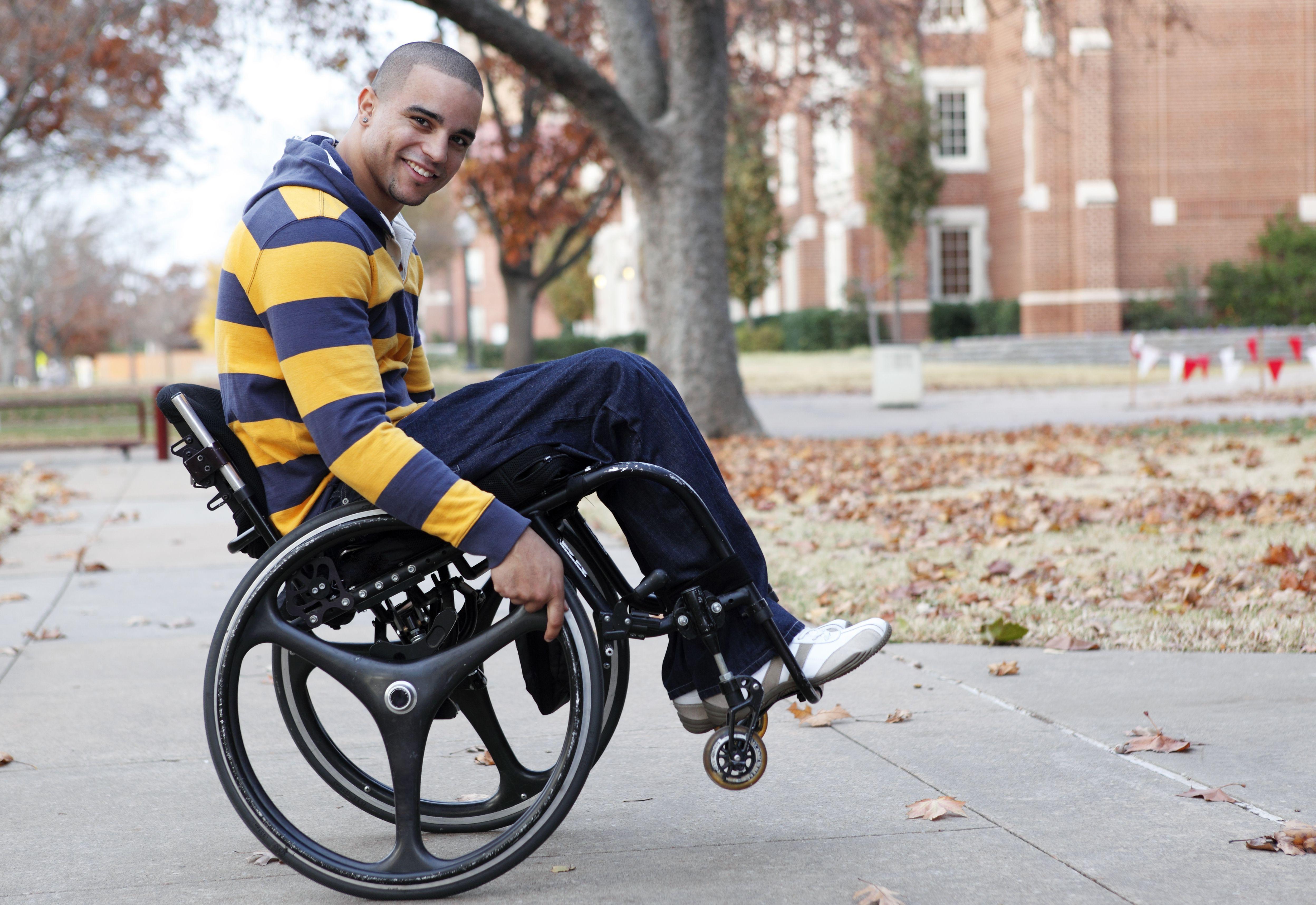 Hombre feliz montado en una silla de ruedas activa haciendo un wheelie