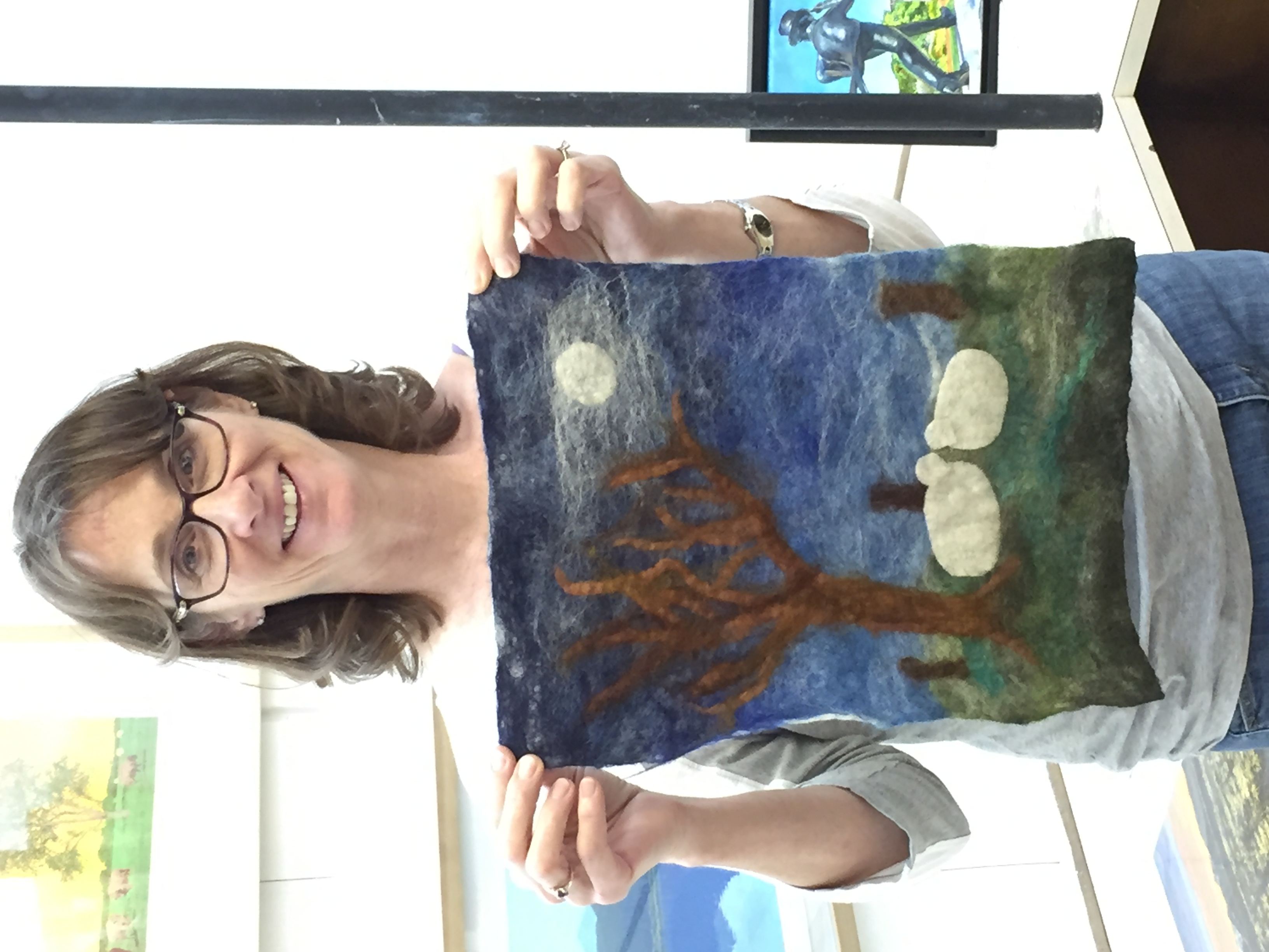 Woman with glasses holding a mini master piece a felted work of art with a tree (no leaves) bright moon night time scene with two white sheep under the tree