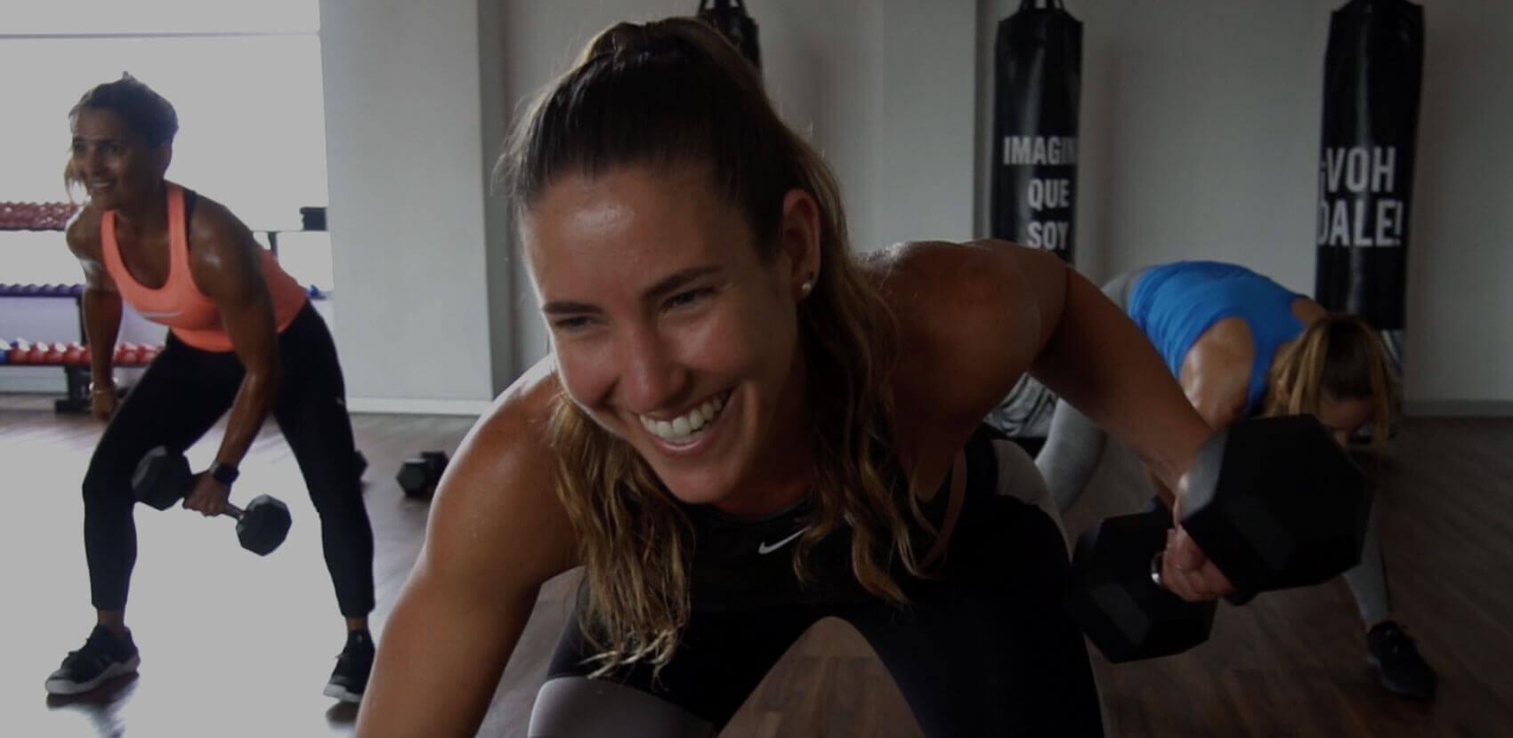 Mujer sonriente levanta una pesa al hacer entrenamiento funcional